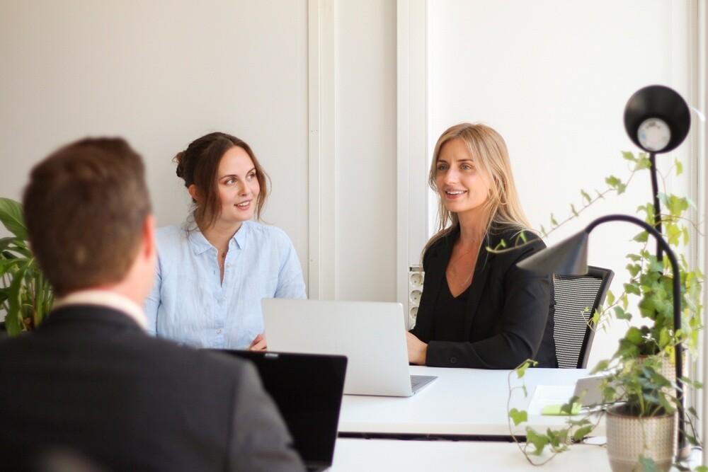 tre kollegor sitter på kontoret och pratar