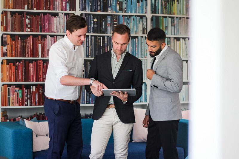 Tre kollegor arbetar på en surfplatta i kontorsmiljö