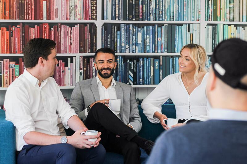 Tre personer sitter i en soffa och pratar