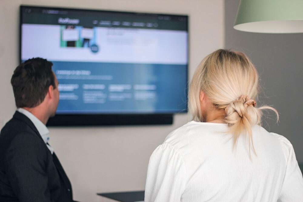 Två kollegor tittar på en presentation