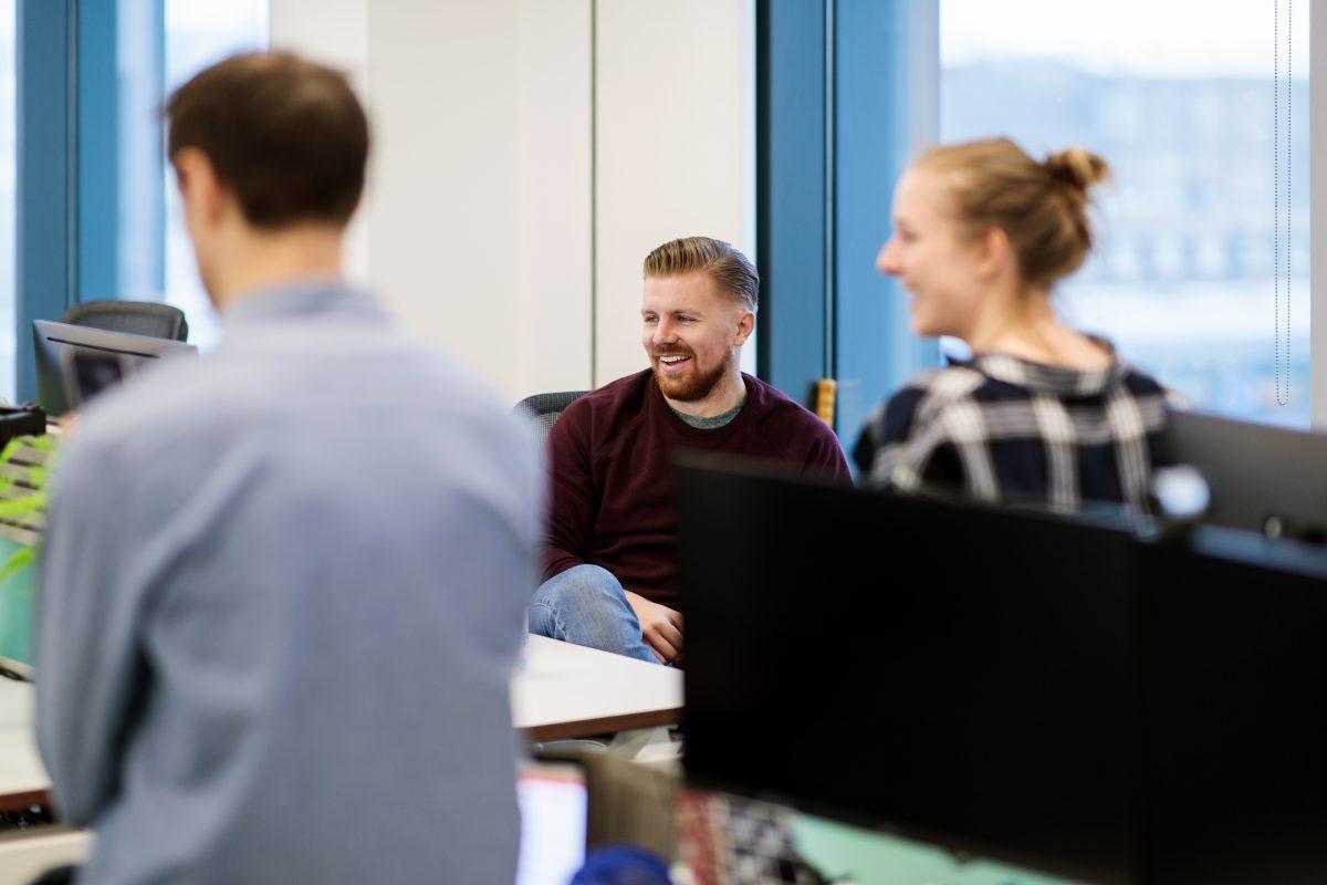Tre kollegor arbetar vid en datorskärm i ett ljust kontorslandskap