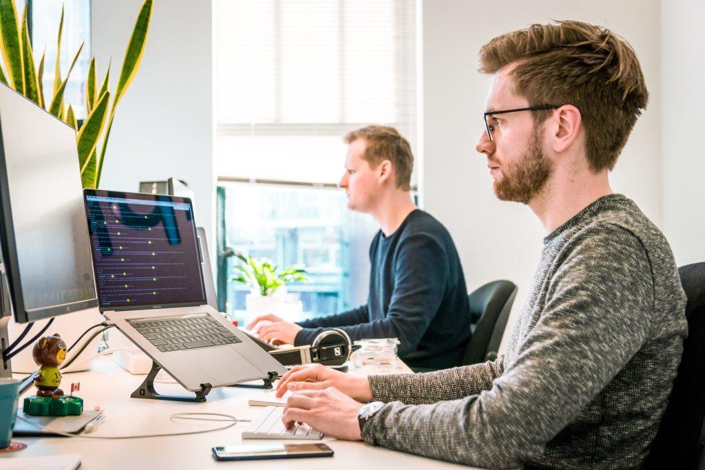 Kundupplevelse. Två personer arbetar framför sina datorer.