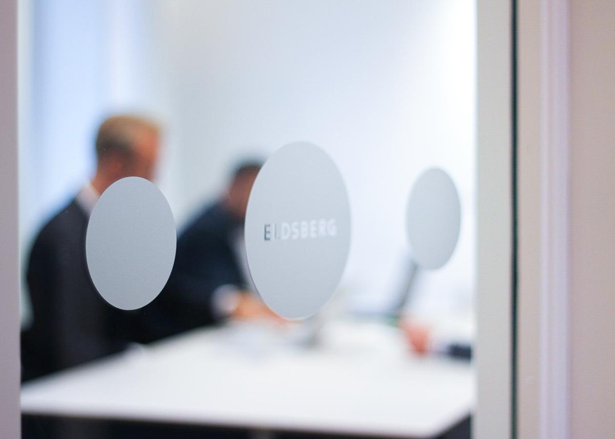 """Fotografi på mötesrum med text""""ELdsberg"""" i förgrunden. I bakgrunden ses personer sitta i rummet och arbeta."""