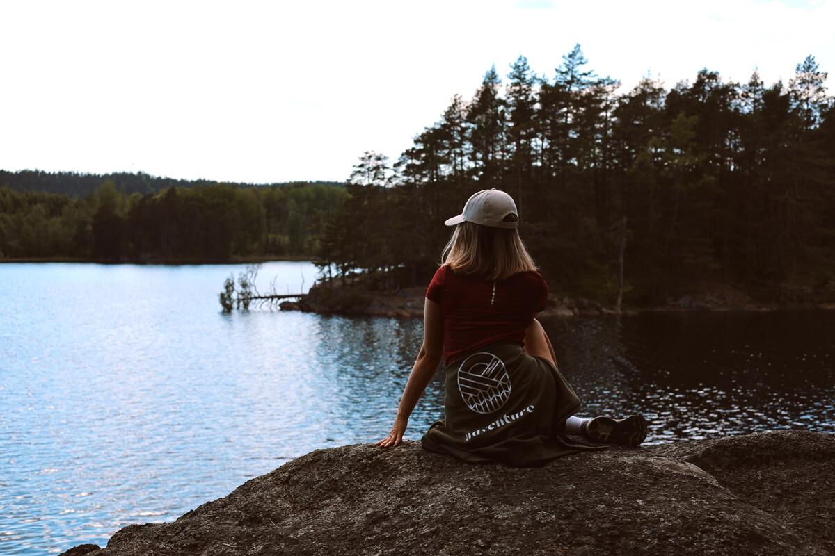 Kvinna med keps och kortklippt hår sitter på en klippavsats och ser ut över sjö