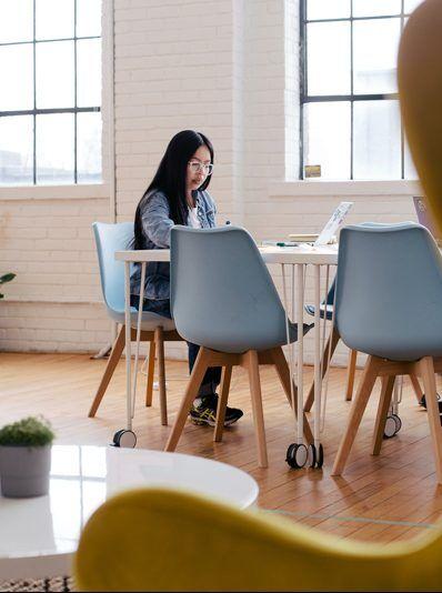 Kvinna med mörkt hår och glasögon sitter vid skrivbord och arbetar. I bakgrunden syns stora fönster och i förgrunden skymtar en gul fotölj.